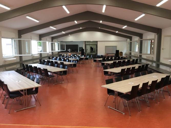 Großer Saal mit modernen Tischen und Stühlen